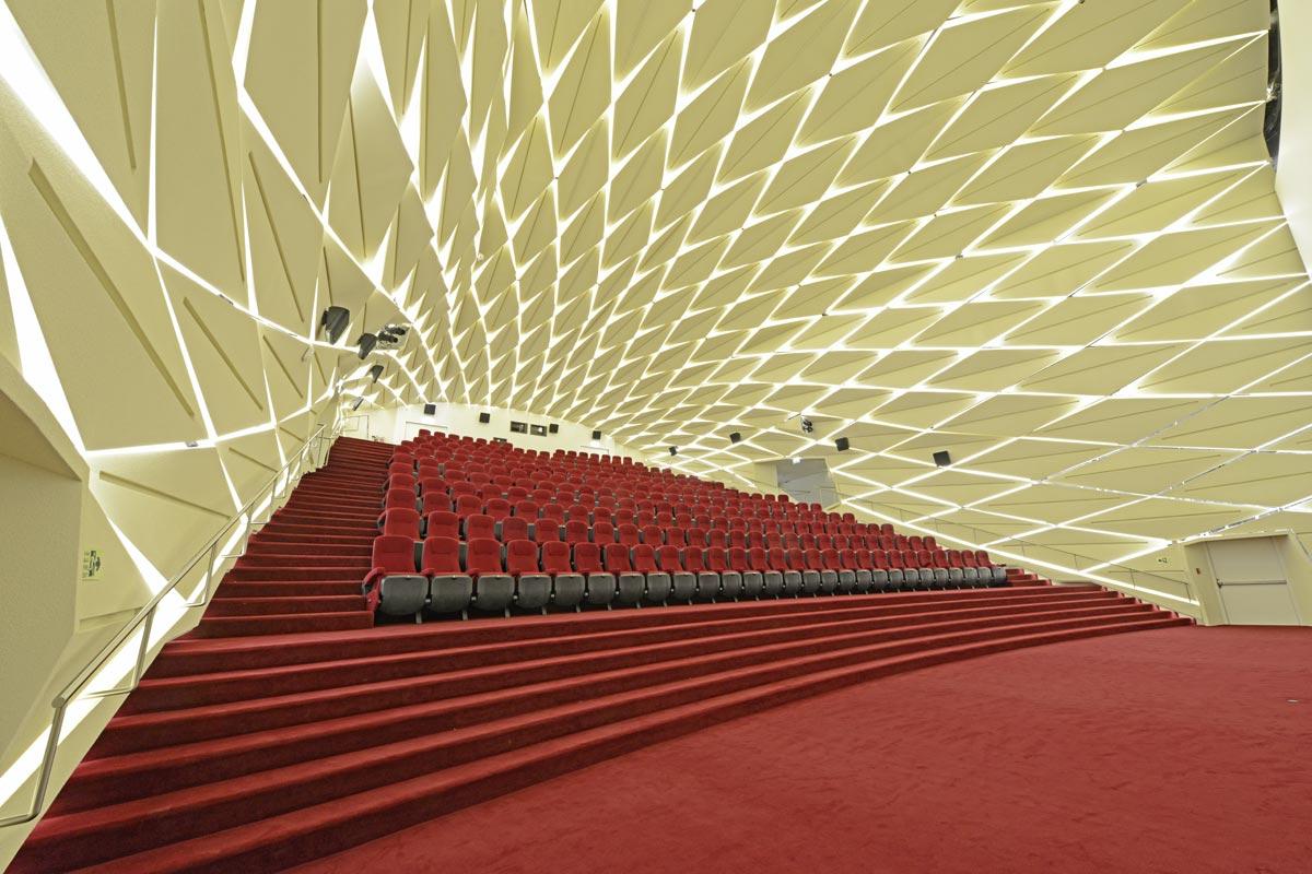 Die CAD generierte parametrische Geometrie der Wand- und Deckenverkleidung erzeugt ein Himmelsgewölbe über den Sitz- reihen. Die Paneele werden mittels LED-Streifen beleuchtet. Foto: Chalabi Architekten & Partner